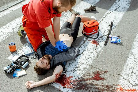 Ambluence worker applying emergency care to the injured bleeding man lying on the pedestrian crossing after the road accident Stock Photo