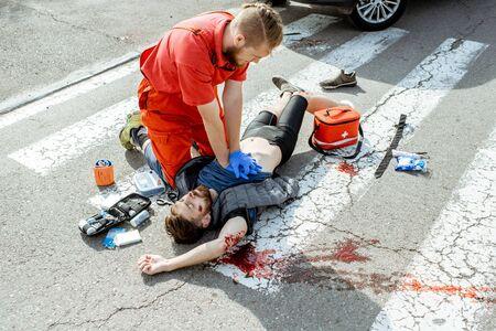 Travailleur d'ambulance appliquant des soins d'urgence à l'homme saignant blessé allongé sur le passage pour piétons après l'accident de la route