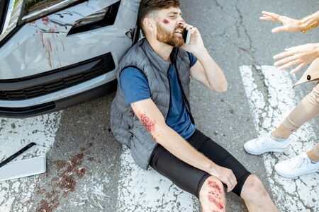 Woman driver with injured man talking phone, while suffering near the broken car on the pedestrian crossing after the accident Stockfoto