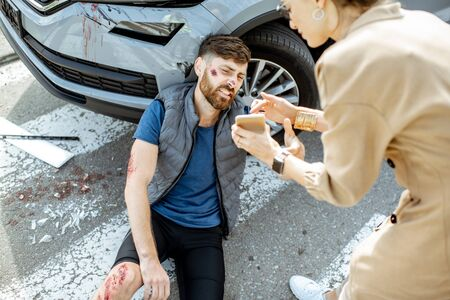 Woman driver calling phone and feeling sorry about injured man suffering on the pedestrian crossing after the road accident Stockfoto