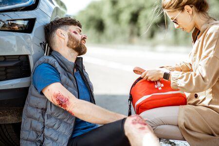 Conducteur se dépêchant avec une trousse de premiers soins pour aider un homme blessé avec des plaies saignantes assis près de la voiture après l'accident de la route