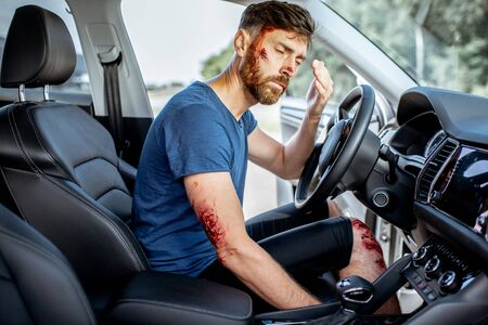Fastened driver with deep bleeding injuries feeling shocked after the road accident inside the car