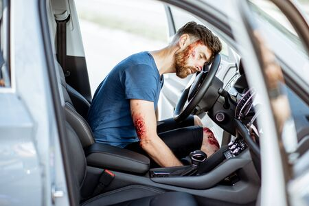 Injured man with a broken head and bleeding wounds sitting on the driver seat without consciousness after the road accident inside the car