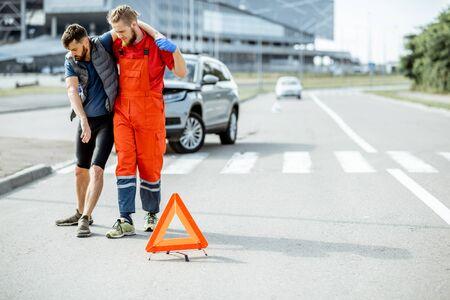Médecin en uniforme aidant un homme blessé à marcher, appliquant les premiers soins après l'accident de la route