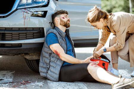 Conducteur se dépêchant avec une trousse de premiers soins pour aider un homme blessé avec des plaies saignantes assis près de la voiture après l'accident de la route Banque d'images