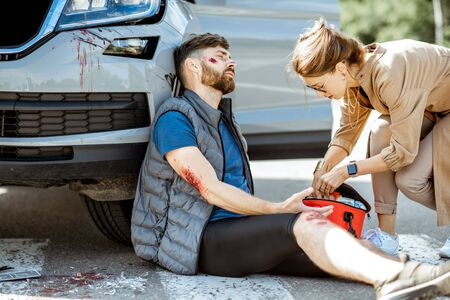 Driver hurrying with first aid kit to help injured man with bleeding wounds sitting near the car after the road accident