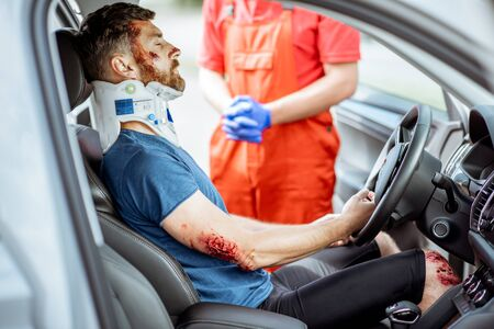 Injured man with deep wounds and corset on his neck sitting on the driver seat during the medical assistance after the accident