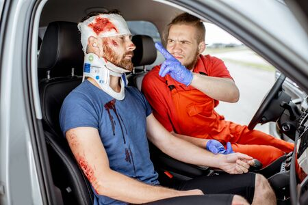 Medic examining injured man with serious damages sitting in the car after the road accident, providing emergency medical assistance