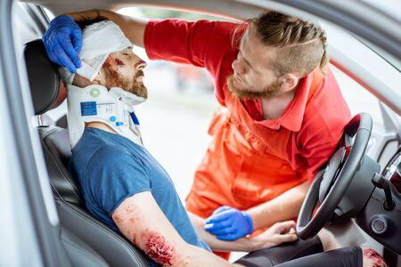 Medics wearing neck corset to an injured man sitting in the car after the road accident, providing emergency medical assistance Фото со стока - 127689570