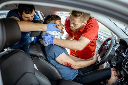 Medics wearing neck corset to an injured man sitting in the car after the road accident, providing emergency medical assistance Фото со стока