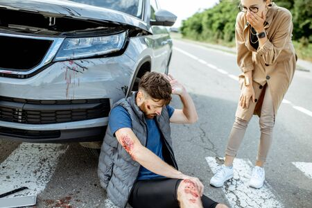 Woman driver feeling sorry about injured man suffering on the pedestrian crossing near the car after the road accident