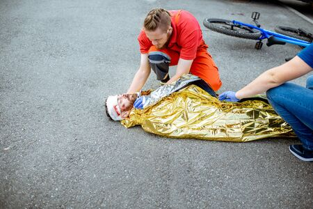 Ambluence worker covering injured man with thermal blanket, providing emergency care after the road accident