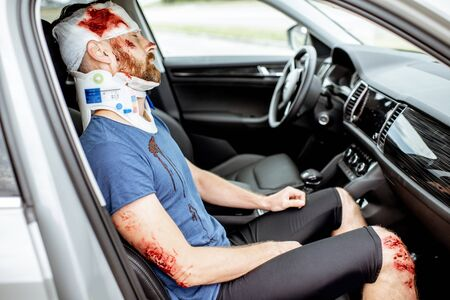 Injured man with deep wounds and corset on his neck sitting on the passenger seat during the medical assistance after the accident
