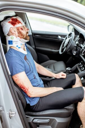 Injured man with deep wounds and corset on his neck sitting on the passenger seat during the medical assistance after the accident Фото со стока - 127689595