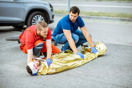Ambluence workers covering injured man with thermal blanket, providing emergency care after the road accident