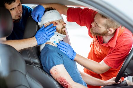 Medics wearing neck corset to an injured man sitting in the car after the road accident, providing emergency medical assistance Stockfoto