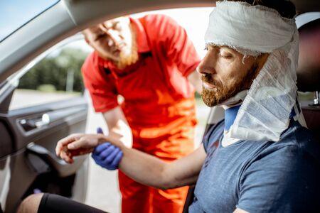 Sanitäter untersucht verletzten Mann mit schweren Schäden, der nach dem Verkehrsunfall im Auto sitzt und medizinische Nothilfe leistet