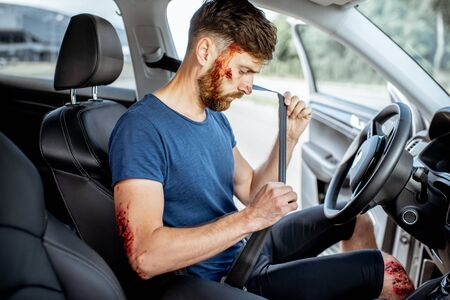 Fastened driver with deep bleeding injuries after the road accident inside the car, feeling safe with security belt