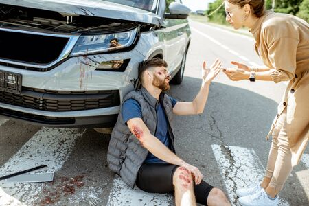 Injured man arguing with woman driver, suffering near the broken car after the road accident on the pedestrian crossing