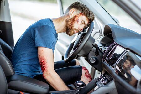 Homme blessé avec une tête cassée et des plaies saignantes assis sur le siège du conducteur sans conscience après l'accident de la route à l'intérieur de la voiture