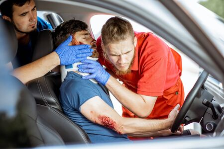 Medics wearing neck corset to an injured man sitting in the car after the road accident, providing emergency medical assistance Imagens