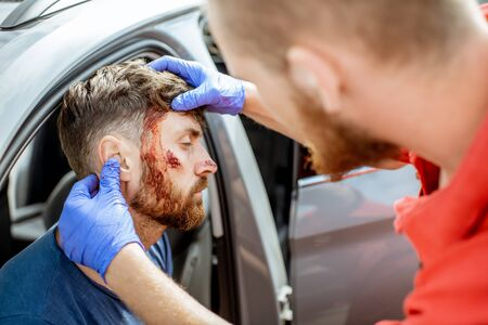 Ambulance worker examining facial injuries of a man sitting near the car after the road accident, providing emergency medical assistance Stockfoto