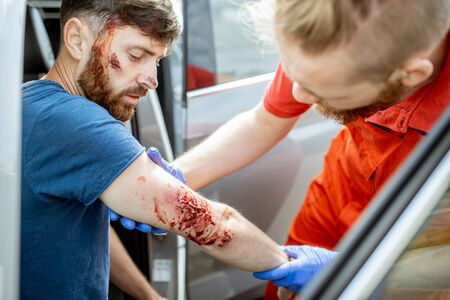 Ambulance worker examining deep arm injuries of a man sitting near the car after the road accident, providing emergency medical assistance