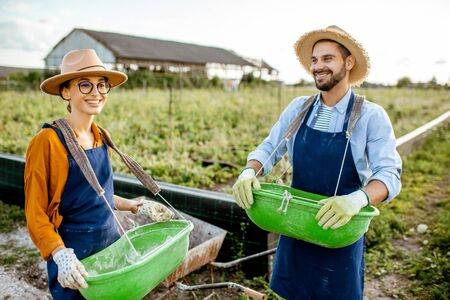 Portrait of a well-dressed farmers standing on the farmland with green buckets for feeding snails on a farm outdoors. Concept of agribusiness and farming