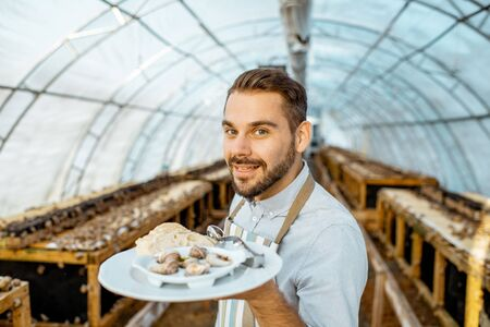 Portrait of a handsome chef cook standing with cooked snails in the hothouse of a farm for growing snails. Restaurant with own production of snails