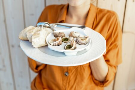 Close-up of a plate with stuffed snails and bread holding in hands Stockfoto