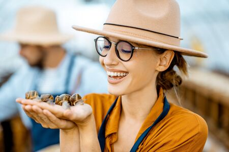 Close-up portrait of a young woman holding snails, taking care of them in the farm for snails growing