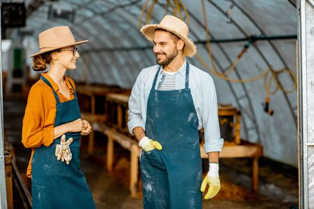 Two well-dressed farmers or agronomists talking together in the hothouse for snails growing on a farm