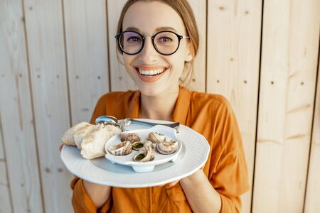 Portrait of a young and cheerful woman holding plate with stuffed snails and bread on a wooden background