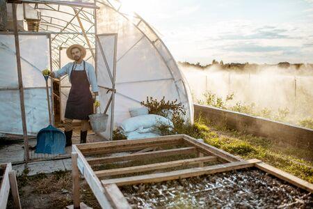 Agriculteur bien habillé avec des outils de travail debout sur une terre agricole avec arrosage automatique dans une ferme au coucher du soleil Banque d'images
