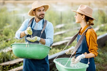 Well-dressed farmers standing on the farmland with green buckets for feeding snails on a farm outdoors. Concept of agribusiness and farming Stok Fotoğraf - 127936219