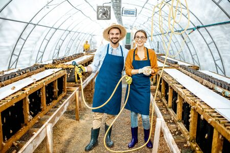 Portrait of a happy workers standing in the hothouse on a farm for growing snails. Concept of farming snails for eating Stock fotó - 127936275