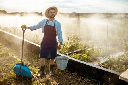 Well-dressed farmer with working tools standing on a farmland with automatic watering on a farm during the sunset Imagens