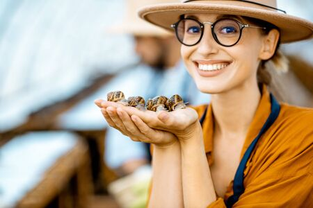 Close-up portrait of a young woman holding snails, taking care of them in the farm for snails growing Banco de Imagens - 127936290