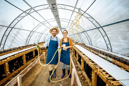 Portrait of a happy workers standing in the hothouse on a farm for growing snails. Concept of farming snails for eating
