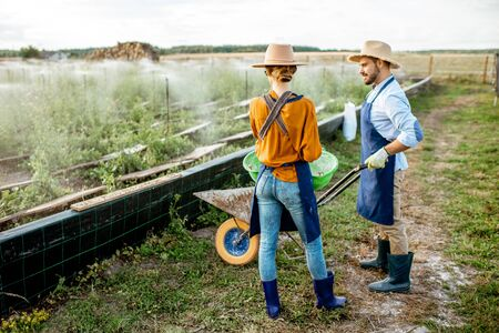 Well-dressed farmers standing on the farmland with green buckets for feeding snails on a farm outdoors. Concept of agribusiness and farming