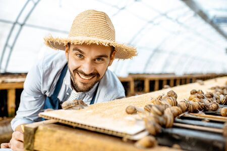 Handsome farmer taking care of snails, examining growing process in the hothouse of the farm. Concept of farming snails for eating