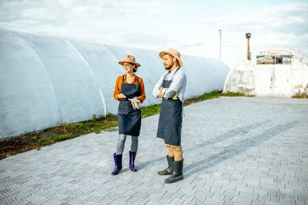 Two well-dressed farmers or agronomists standing on a farm with hothouses on the background Imagens