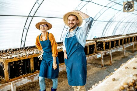 Portrait of a two happy well-dressed farmers standing in the hothouse on a farm for growing snails. Concept of farming snails for eating