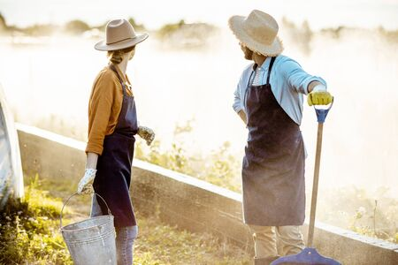 Two well-dressed farmers with working tools standing on a farmland with automatic watering on a farm during the sunset Stok Fotoğraf - 127936350