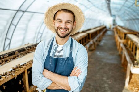 Portrait of a well-dressed farmer standing in the hothouse on a farm for growing snails. Concept of farming snails for eating