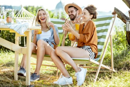 Young friends talking and having fun, while sitting together with summer drinks on the sunbeds at the backyard during the sunny day 版權商用圖片