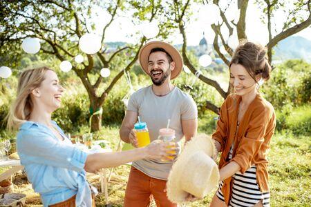 Giovani amici che si divertono, in piedi insieme a un drink nel cortile o giardino splendidamente decorato durante un pranzo o una festa festivo