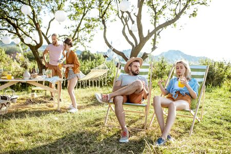 Young and cheerful friends relaxing with drinks, sitting on the sunbeds in the beautifully decorated backyard or garden during a festive meeting
