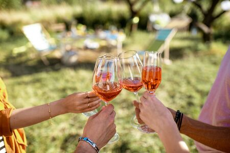 Friends clinking wine glasses in the garden with beautifully decorated dinning place, close-up view 版權商用圖片