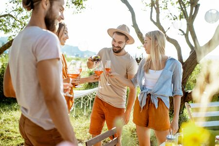 Young and cheerful friends having fun, drinking wine in the beautifully decorated backyard during a festive meeting or party on a sunny summer evening Stock Photo - 128768899